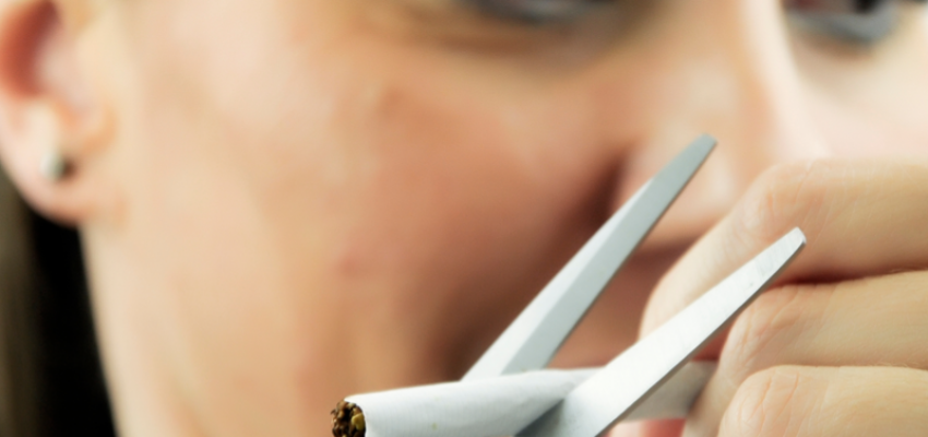 Young woman is determined to quit smoking. She is trying to cut the cigarette with scissors